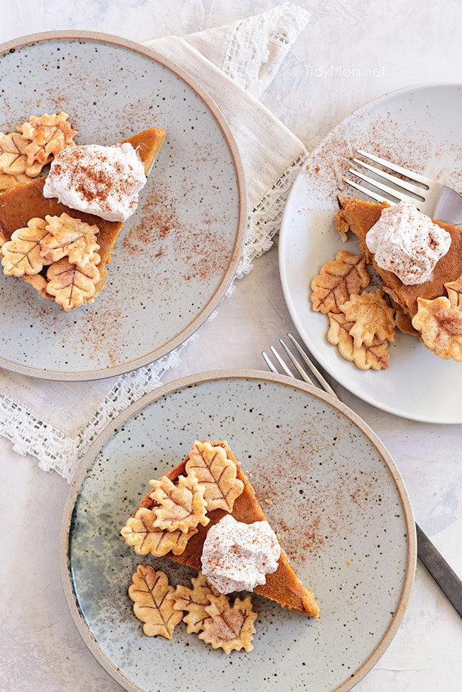 three pumpkin pie slices with cinnamon whipped cream