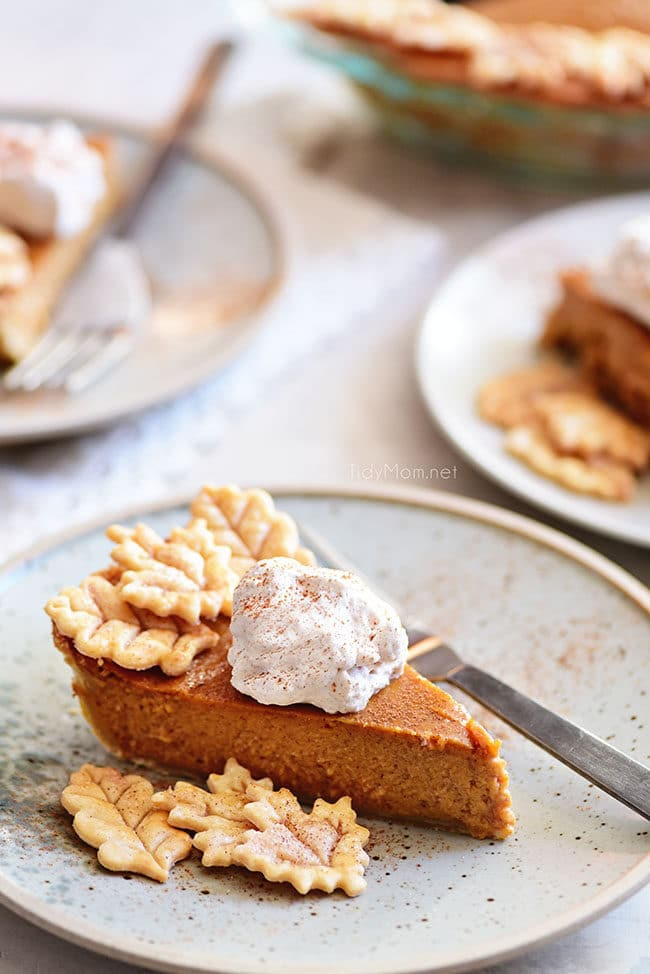 pumpkin pie with leaf cut-outs and whipped cream