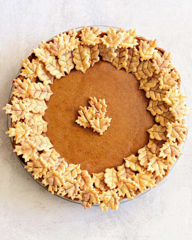 a whole pumpkin pie with leaf cut-outs