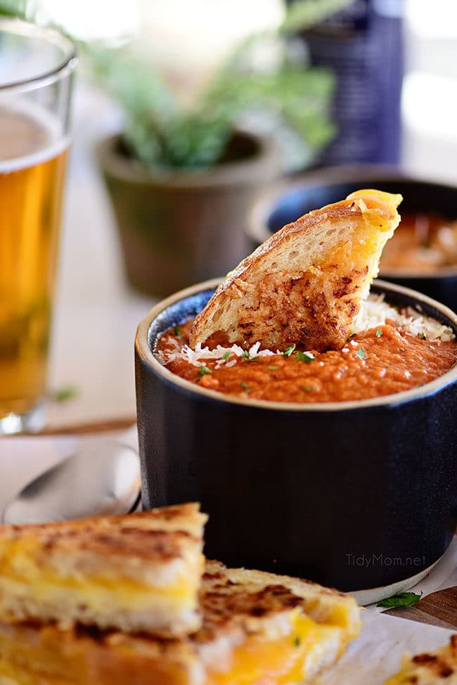 Roasted Tomato Soup in a black mug with grilled cheese sandwich