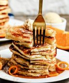 a fork digging into a stack of pancakes