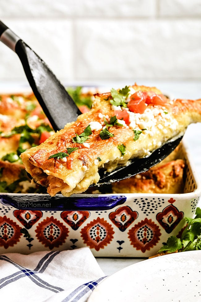 serving enchiladas from a baking dish