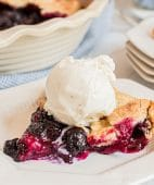 blueberry galette with a scoop of vanilla ice cream on a white plate