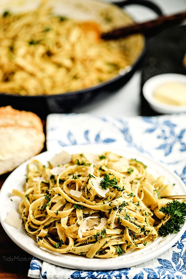 fettuccine alfredo on a plate with blue and white napkin