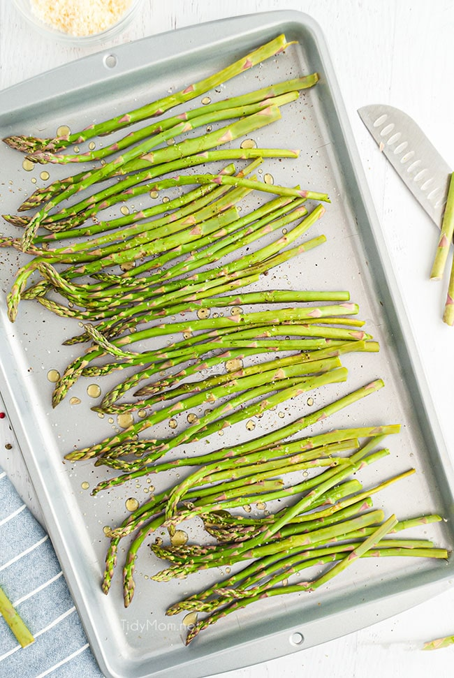 asparagus laid out on a baking sheet with a drizzle of olive oil