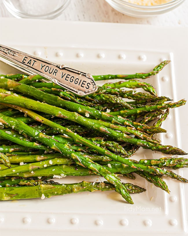 "baked asparagus on a plate with tongs that says ""eat your vegetables"""