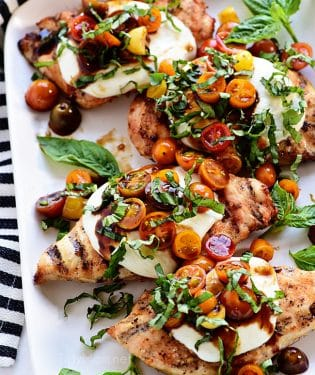platter of grilled chicken breasts topped with caprese salad