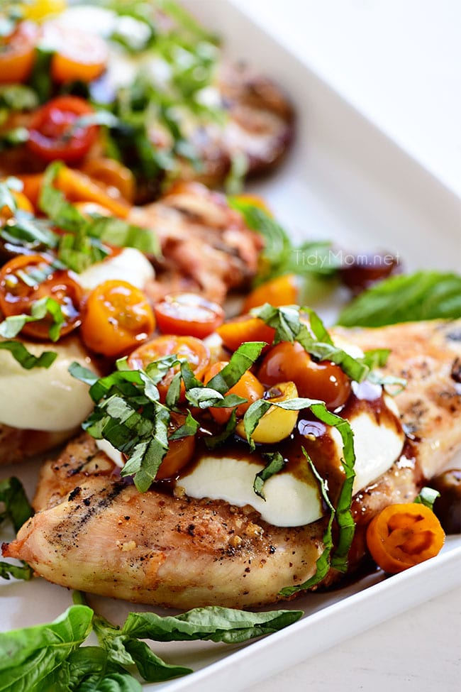 grilled chicken breasts topped with mozzarella, tomatoes and basil