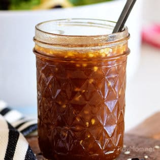 Canning jar with Honey Sesame Asian Salad Dressing and a spoon