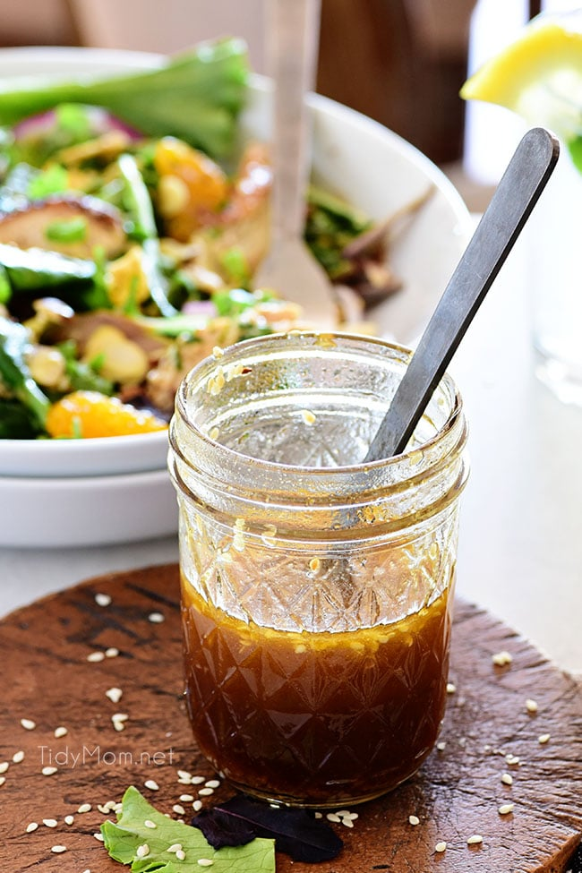 Honey Sesame salad dressing in a jar new to a bowl of salad