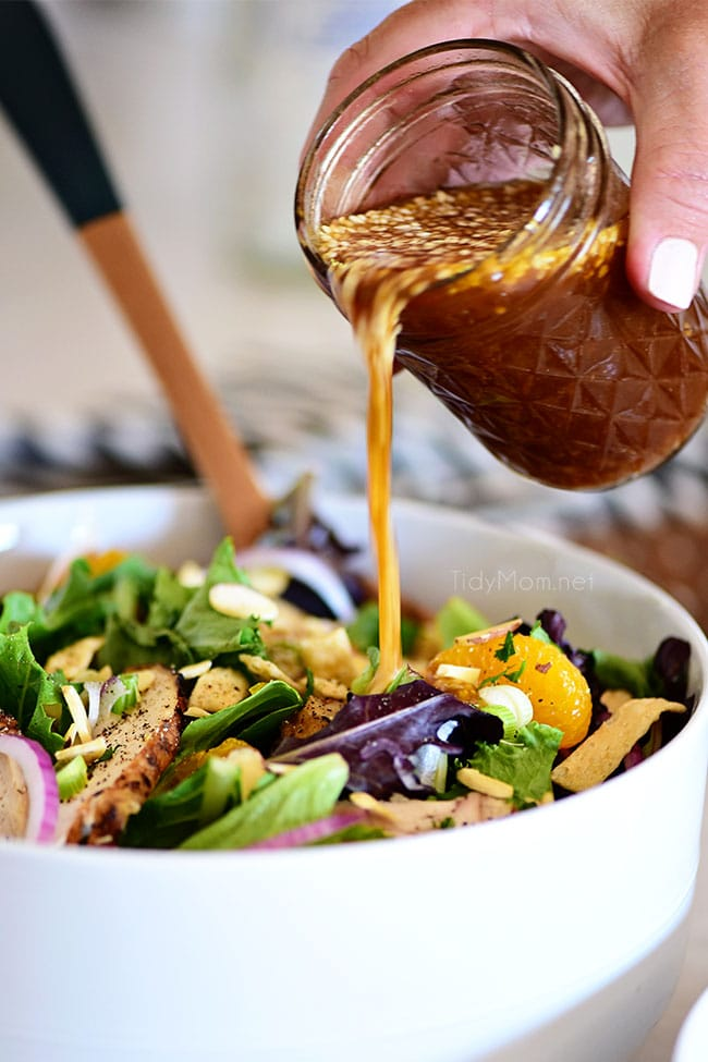 pouring Asian salad dressing over a salad