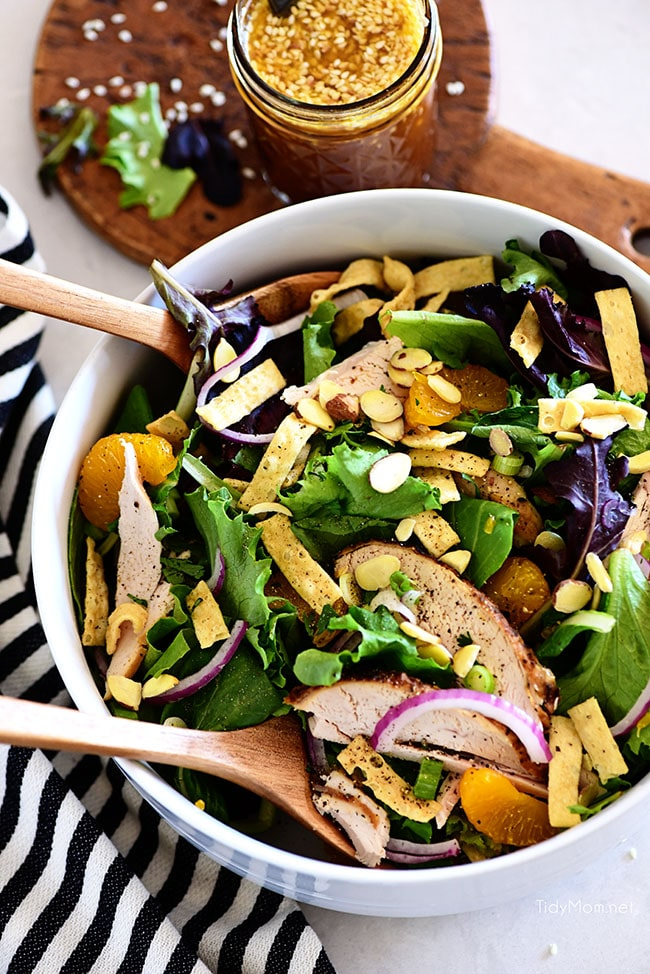 asian chicken salad in a bowl with salad spoons