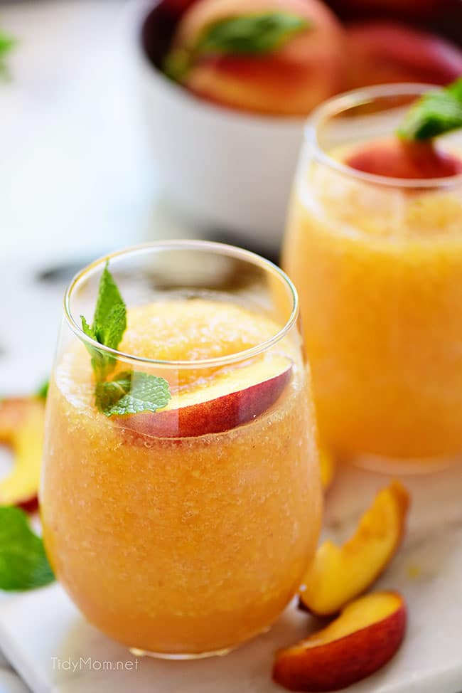 two frozen peach slush cocktails with fresh peach garnish