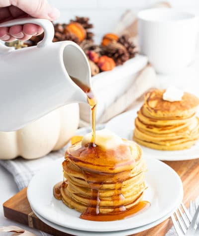 Pouring syrup on stack of pancakes with butter on plate
