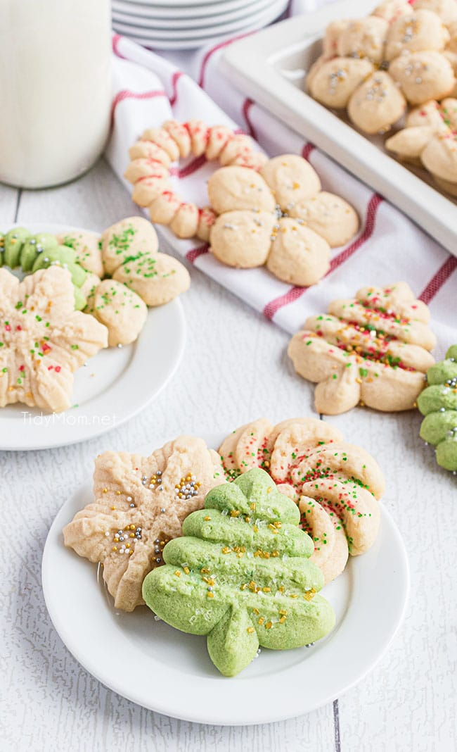 Holiday spritz cookies on a plate with a glass of milk