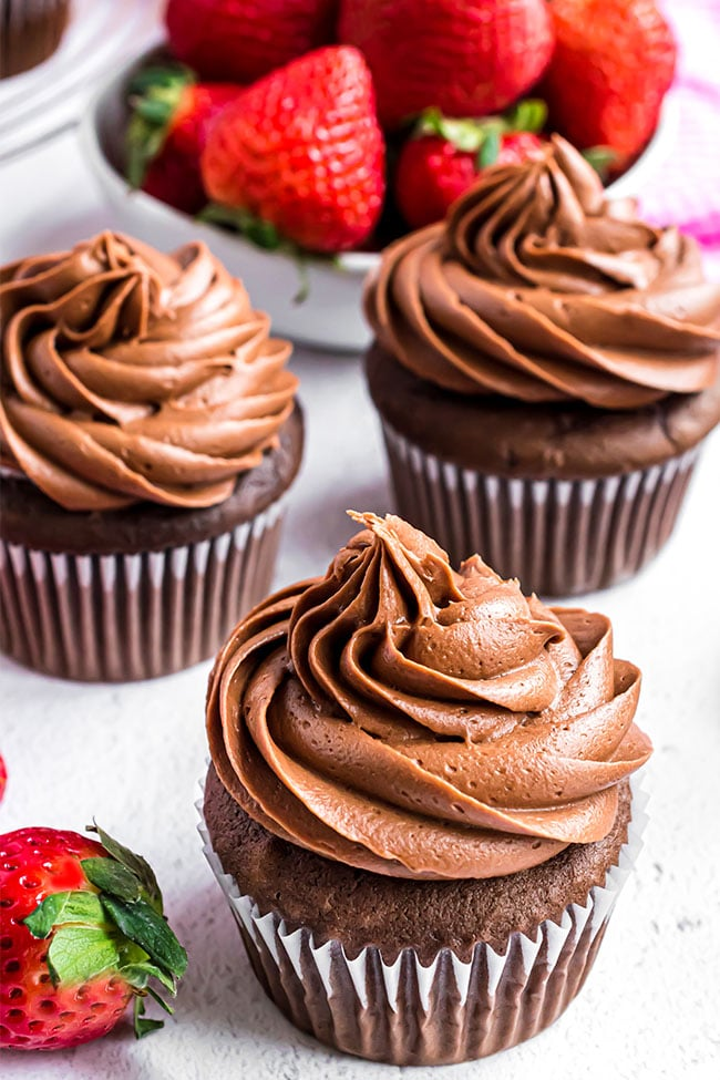 3 chocolate cupcakes with chocolate frosting