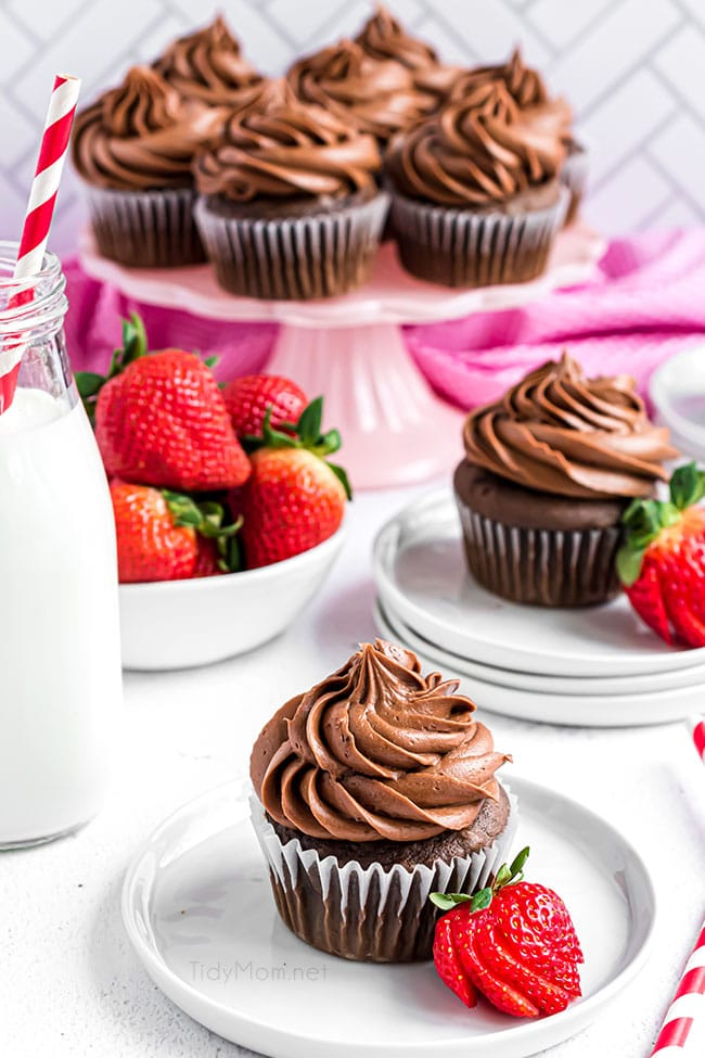 chocolate cupcakes with chocolate frosting and strawberries on plates