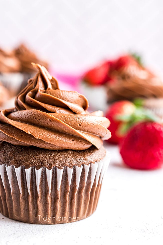 chocolate cupcake with strawberries in background