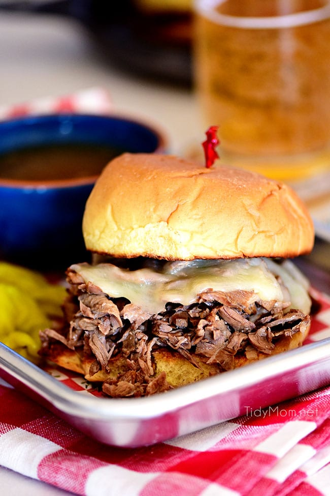 Italian beef sandwich with cheese and a bowl of au jus