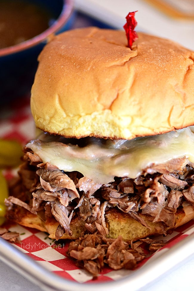 Italian beef sandwich with cheese on a red checked tray