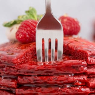 a fork going into a big stack of red pancakes