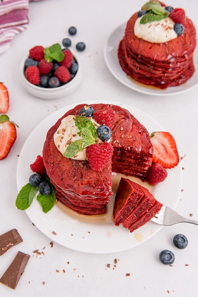 A stack of red velvet pancakes with the first bite on a fork