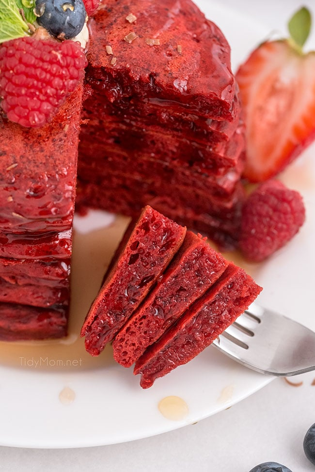 red velvet pancakes with the first bite on a fork