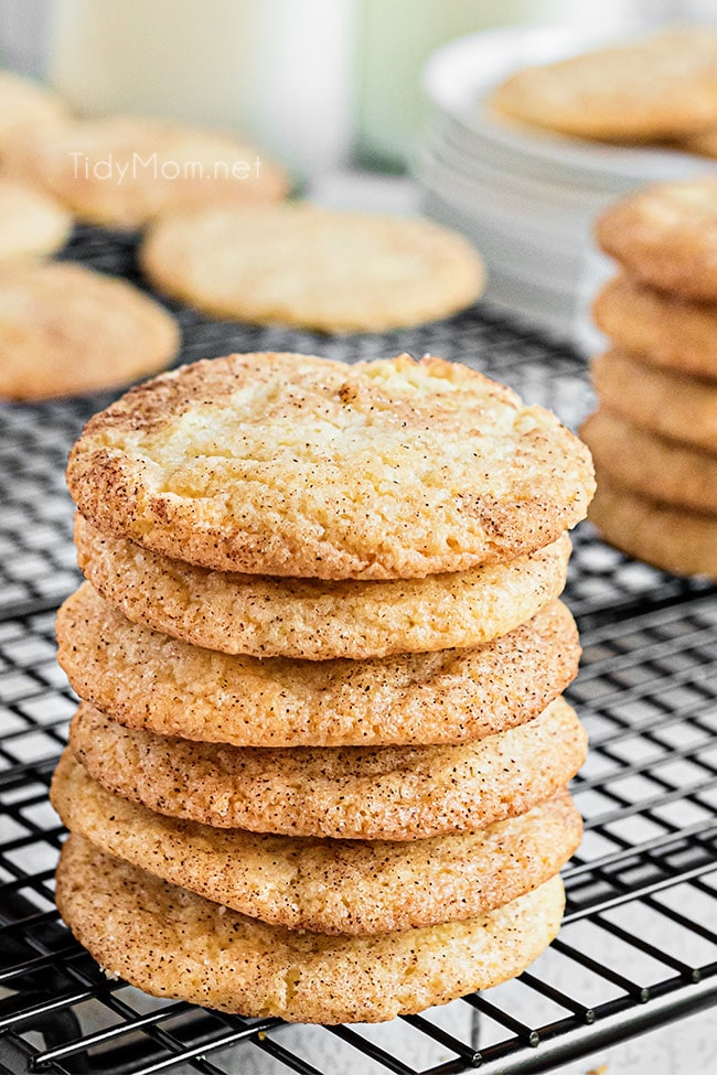 Six snickerdoodles stacked together sitting on a cooling rack