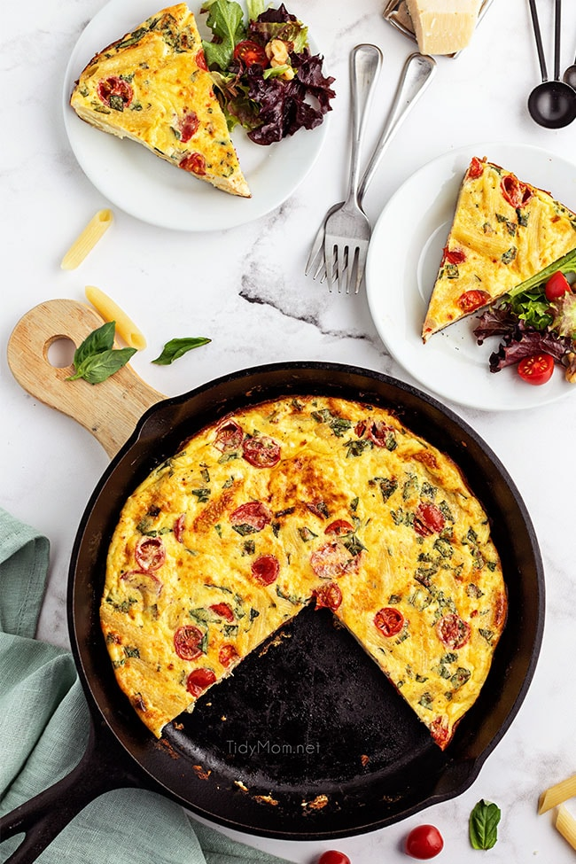 frittata in cast iron skillet with 2 servings on plates