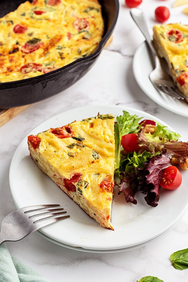 frittata serving on a plate with a salad