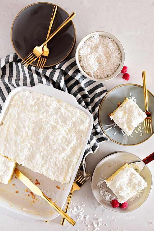 coconut cake in pan with three pieces served on plates