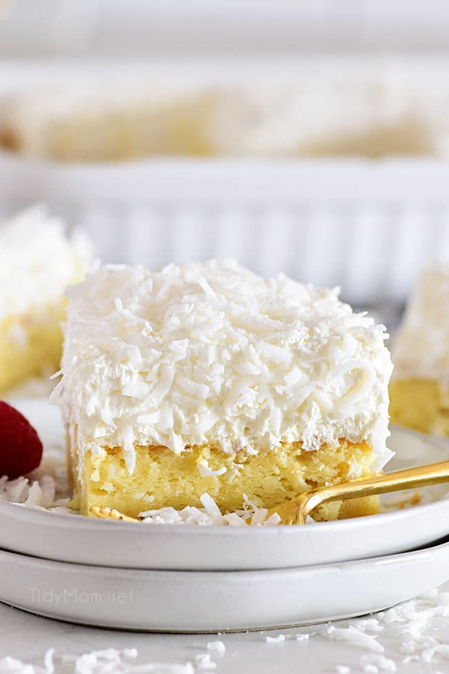 Slice of coconut sheet cake on a white plate