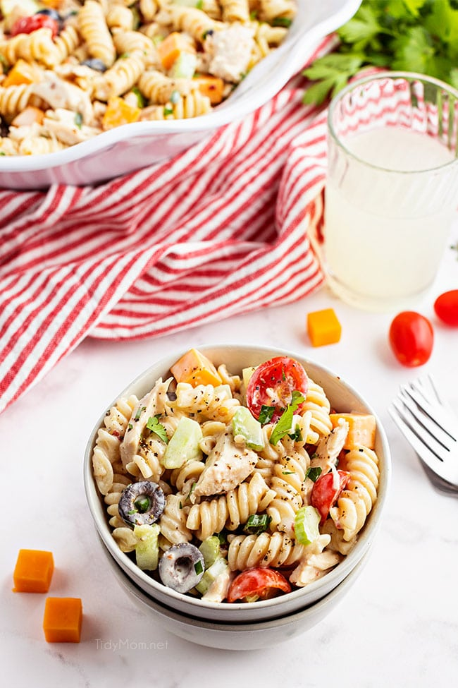 bowl of pasta salad with chicken and a red striped napkin