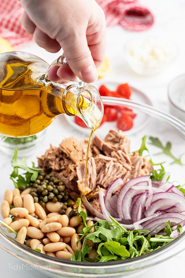 salad ingredients in a bowl and woman drizzling oil over them