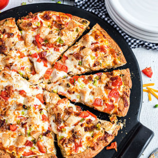 sliced chicken bacon ranch pizza on a pizza pan