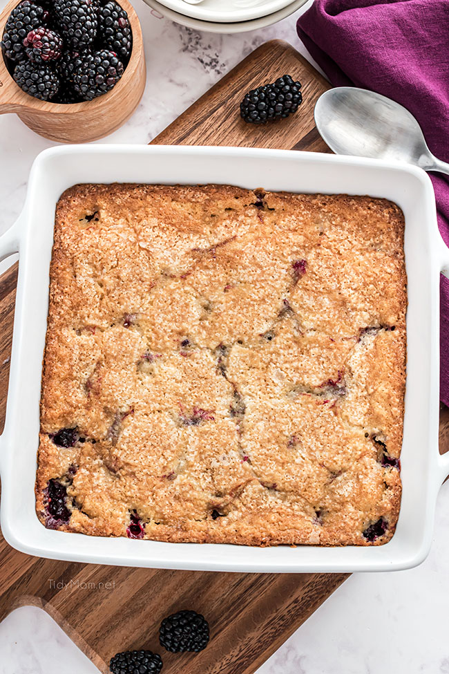 blackberry cobbler in a baking dish with a purple napkin