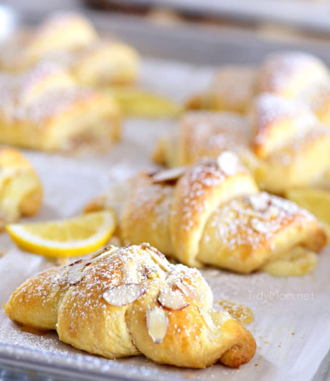 lemon cheesecake crescent rolls with almond slices on a sheetpan