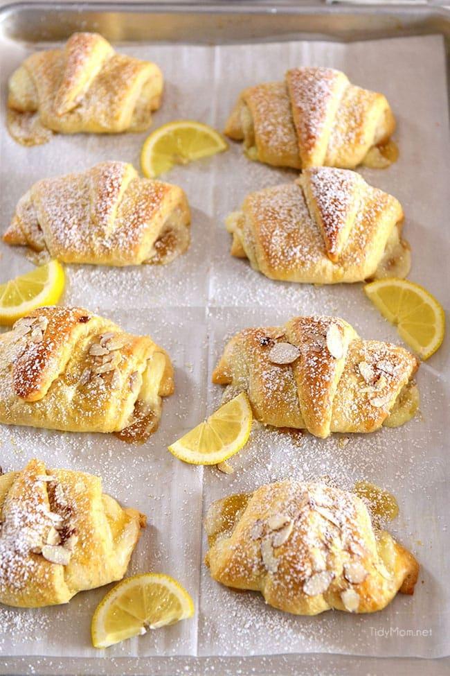lemon cheesecake crescent rolls on a baking sheet with fresh lemon slices