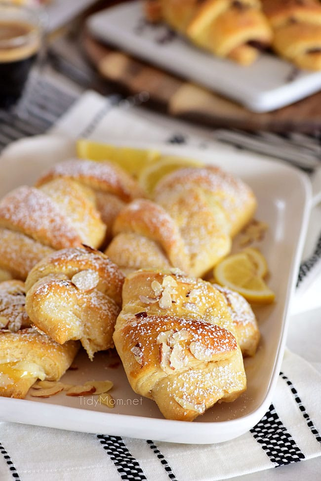 lemon cheesecake crescent rolls with powdered sugar and almond slices on a white plate