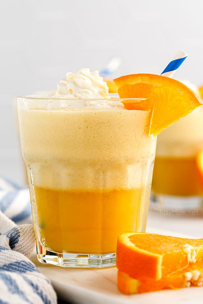 a glass fill with an Orange Julius and topped with whipped cream and fresh orange slice