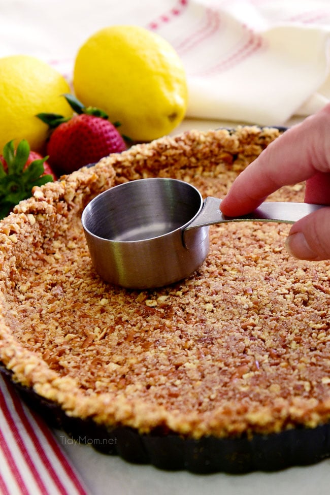 pressing out a pretzel pie crust with a measuring cup