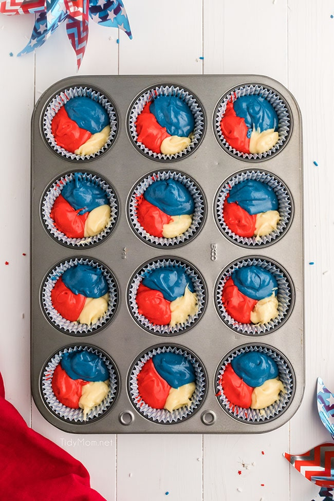 red white and blue cupcake batter in cupcake wells