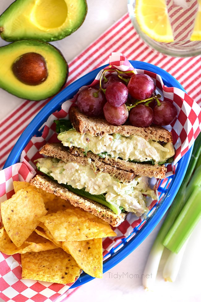 avocado chicken salad sandwich cut in half in a basket with grapes and chips