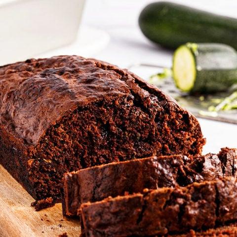 sliced loaf of chocolate zucchini bread on a cutting board