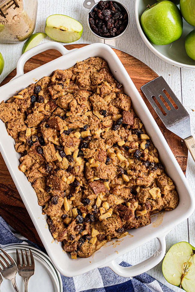 A white baking dish with warm apple bread pudding