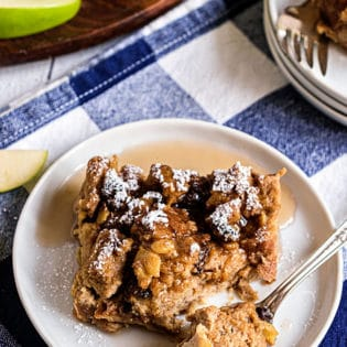 peanut butter apple bread pudding on a white plate with a blue checked napkin