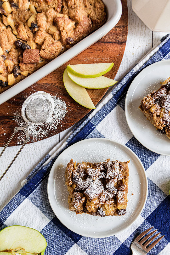 apple bread pudding with a dusting of powdered sugar on a plate
