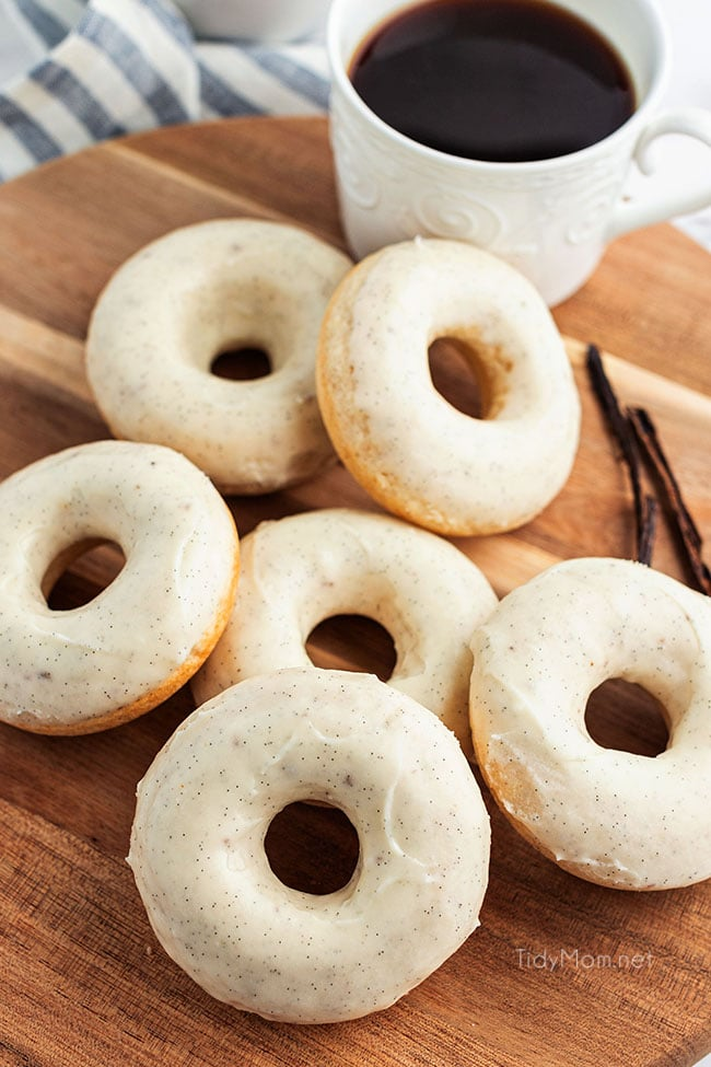 a pile of cinnamon donuts on a wood board with a cup of coffee