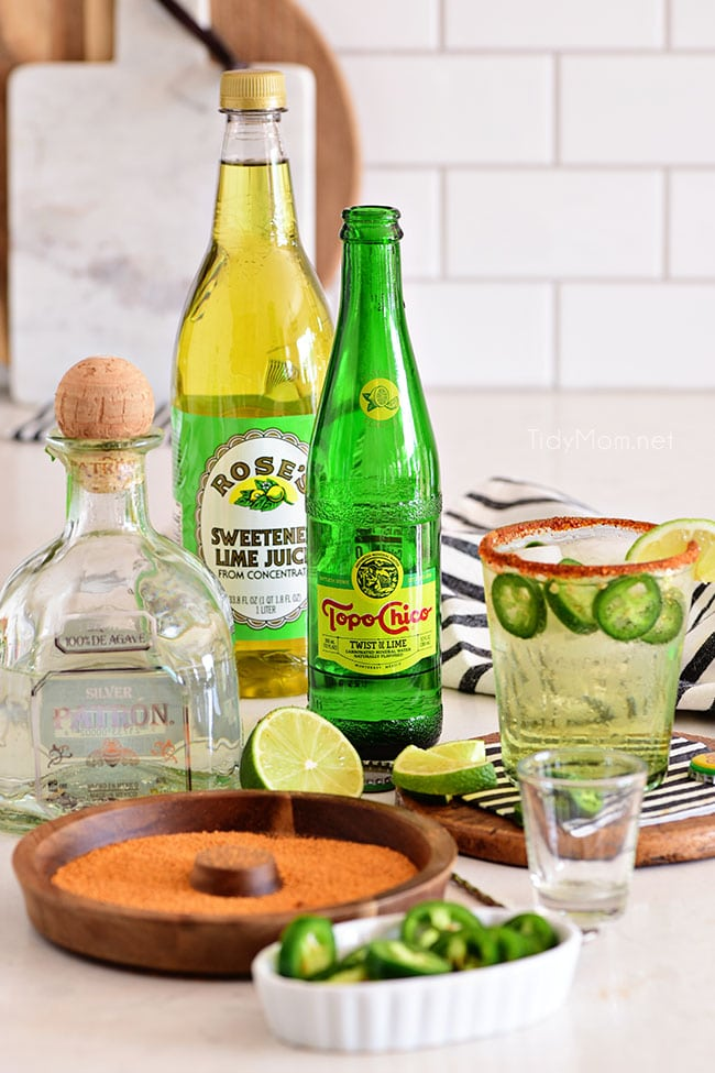 ranch water ingredients - a bottle of tequila, Topo Chico and lime juice on a counter