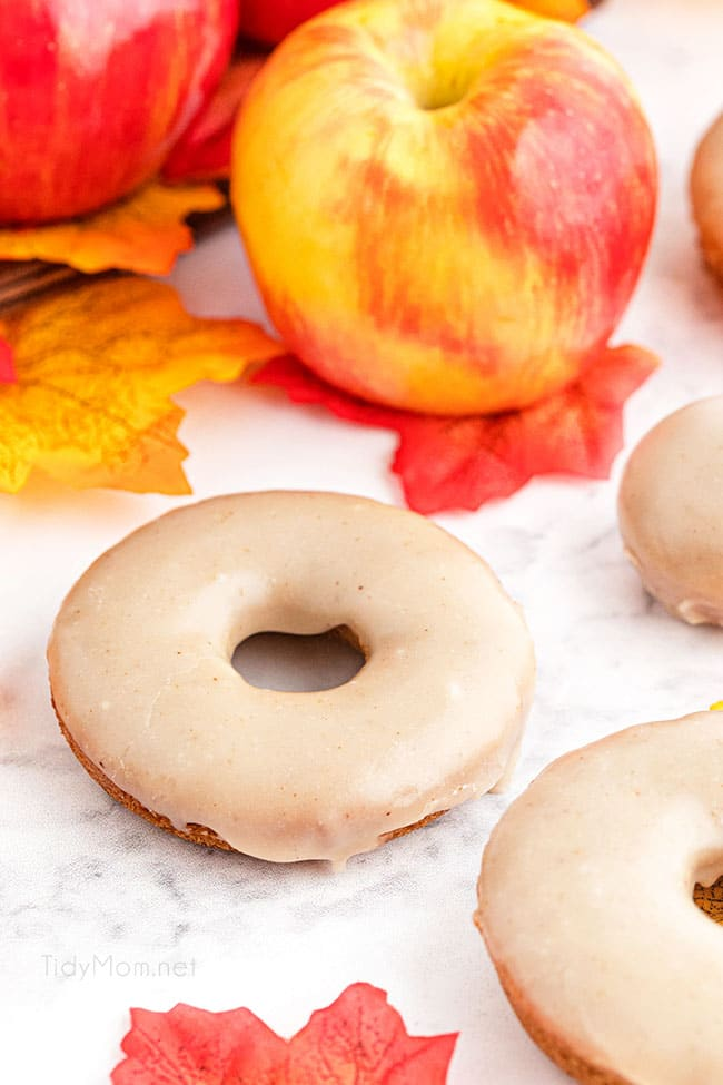 apple cider donuts with a basket of apples and fall leaves